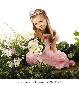 A beautiful preschool princess sitting among flowers and foliage while holding a bouquet.