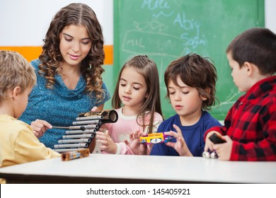 Beautiful preschool teacher teaching students to play xylophone in class