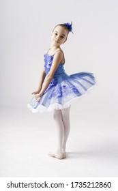Beautiful preteen girl ballerina wearing a princess dress, winter fairy dancing over white background