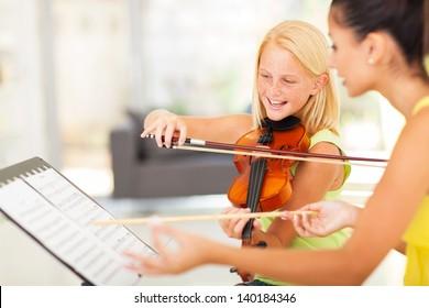 beautiful preteen girl in music class with music teacher