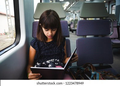 Beautiful preteen girl reading a book while travelling by train