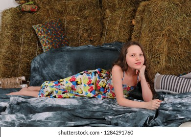 the beautiful preteen girl the teenager in a long color dress smiles and poses in studio at a stack with hay for rural style