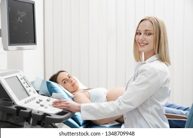 Beautiful, pretty blonde doctor wearing in white medical gown doing ultrasound exam of woman's abdomen. Pregnant woman lying, looking at camera, smiling. Modern ultrasound machine.