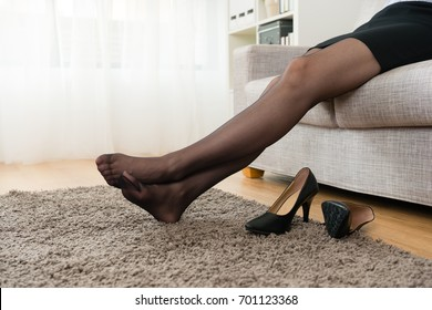 beautiful pretty business woman take off high heel shoes sitting on sofa couch resting when she after work back to home.