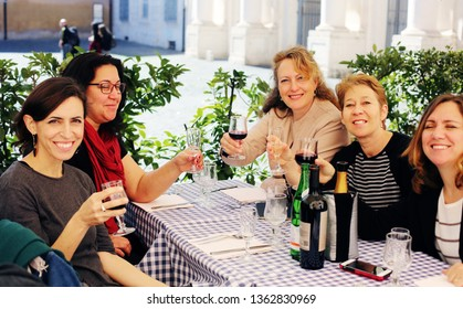 Beautiful pretty caucasian women friends sitting together enjoying warm spring day