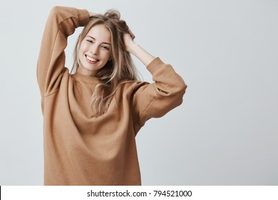 Beautiful pretty charming young blonde woman in loose sweater smiling happily, having fun indoors, playing with long straight hair. Pretty girl looking at camera with joyful smile, rejoicing life