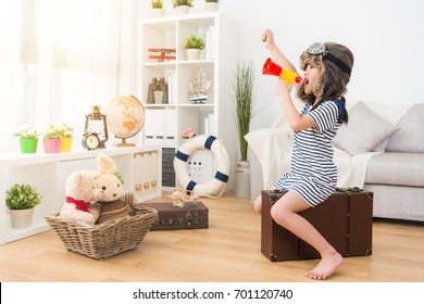 beautiful pretty female kid children dress up as aviator sitting on retro suitcase in playroom and using loudspeaker shouting announcing preparing go to adventure.