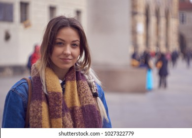 Beautiful pretty girl posing and smiling on the street for photography in Prague.
