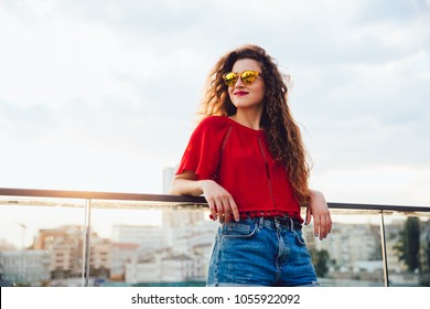 Beautiful pretty girl in sunglasses, with long curly hair standing outdoors, on background of city, looking away. Dressed in red blouse and jeans shorts.