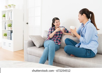 beautiful pretty girls holding hot cup drinking coffee sitting on sofa and looking each other sharing funny things enjoying sisters talking time..