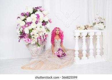 Beautiful, pretty, happy rose long and curly hair woman in wedding dress posing. Model like a doll barbie, in interior studio shooting, with colorfull roses, flowers. Collonade antique background