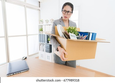 beautiful pretty office worker woman holding personal items box ready leaving company and feeling angry when she received layoff message.