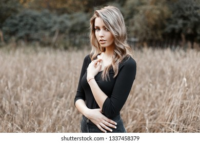 Beautiful pretty sexy young woman in a black stylish T-shirt with blond hair in trendy jeans poses in a field on a warm autumn day. Modern cute girl model walks outdoors.
