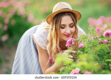 Beautiful pretty woman posing near roses in a garden. The concept of perfume advertising.