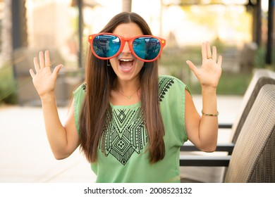 Beautiful Pretty Young Brunette Woman with Hilarious Funny Comical Large Jumbo Sunglasses Looking At Camera with Hands Up with White Teeth Outdoors with Natural Soft Daylight Outdoor Mall Café
