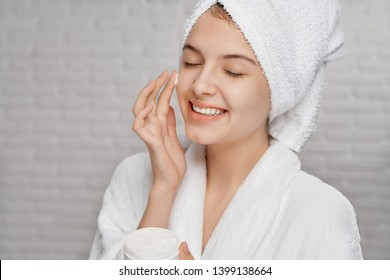 Beautiful, pretty, young woman applying on face cream for skin care. Girl in white bathrobe with towel on head smiling, posing with closed eyes, holding cream for hydrating and rejuvenating of skin.