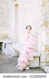 Beautiful princess girl in glamorous pink fashion dress is photographed sitting on Cap FERRAT