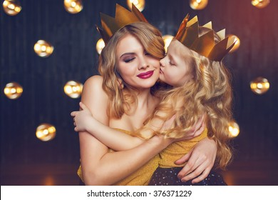 Beautiful princess mother and daughter in a gold crown