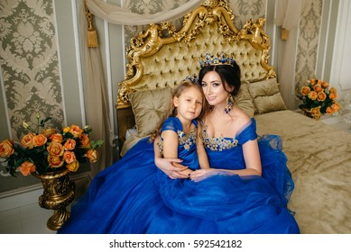 Beautiful princess mother and daughter in a gold crown and luxurious blue dresses