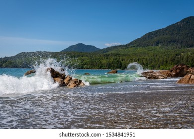 Beautiful pristine Bonanza beach with turquoise waters crashing into the rocks creating a unique spray on a sunny blue sky day in Haida Gwaii, British Columbia, Canada.