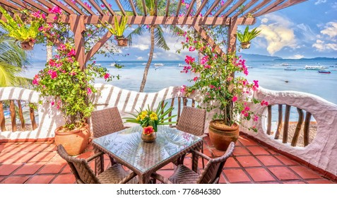 Beautiful private resort balcony with colorful flowers in a vibrant seaside setting on a tropical island, with blue sky and water in the background.