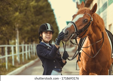 Beautiful professional female jockey standing near horse. woman horse rider is preparing to equitation. girl and horse. equestrian sport concept. dressage horse