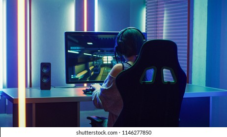 Beautiful Professional Gamer Girl Playing in First-Person Shooter Online Video Game on Personal Computer. Casual Cute Geek Girl Wearing Headset. Dark Room Suddenly Lit by Neon Lights in Retro Style
