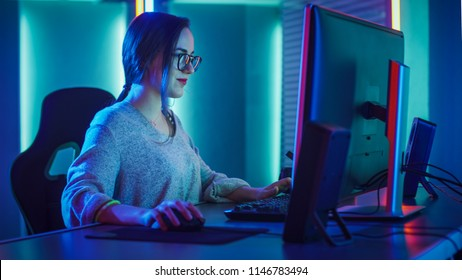 Beautiful Professional Gamer Girl Sitting Down to Play in First-Person Shooter Online Video Game on Her Personal Computer. Casual Cute Geek wearing Glasses and Talking into Headset. Cyber e-Sport.