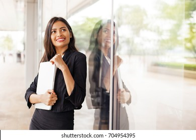 A beautiful professional Indian woman wearing a suit standing holding a laptop and smiling by a glass window