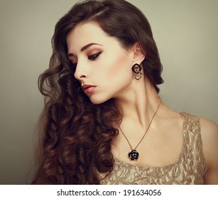 Beautiful profile of female model looking down with long brown curly hair. Vintage portrait