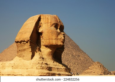 Beautiful profile of the Great Sphinx including pyramids of Menkaure and Khafre in the background on a clear sunny, blue sky day in Giza, Cairo, Egypt. Pyramid Egyptian Sphinx on background of clouds
