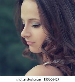 Beautiful profile of romantic girl face looking down outdoors. Closeup portrait
