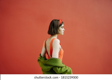 beautiful profile of young skinny girl in red dress and green jacket on background. Emotional bright saturated cheerful color combination. Conceptual artistic composition. Dramatic dreams and hopes