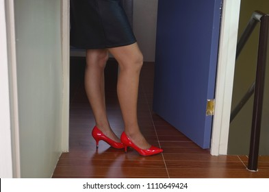 Beautiful prostitute in sexy leather skirt and red high heels is waiting for clients in the door of her room.