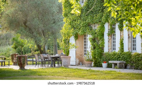 Beautiful Provencal farmhouse in the Camargue countryside. Virginia creeper on the facade, white shutters and a welcoming table on the terrace in front of the house. Golden light on a June evening