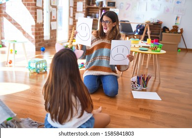 Beautiful pshychologist and toddler doing therapy with emotions emoji around lots of toys at kindergarten