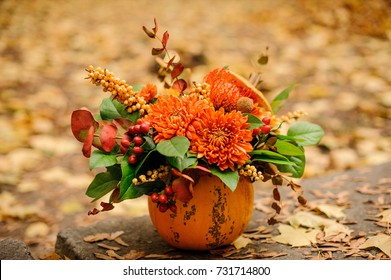 Beautiful pumpkin with a lovely autumn flower composition on the background of yellow fallen leaves