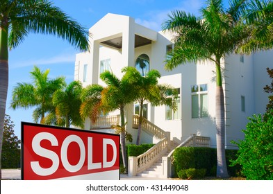 Beautiful purchased luxury residential home with front stairways and lush green palm trees against a blue morning sky with a bright SOLD sign in the front yard.