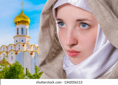 Beautiful pure girl with a clear look in a white scarf addresses prayer to God