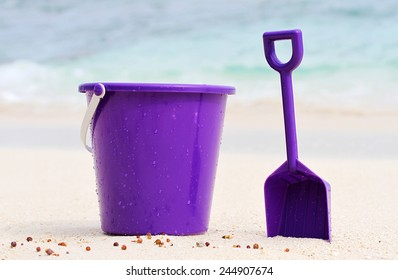A beautiful Purple bucket and spade on an isolated tropical beach