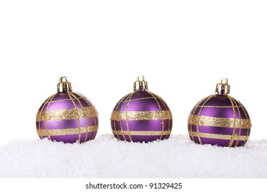 beautiful purple Christmas balls in snow isolated on white