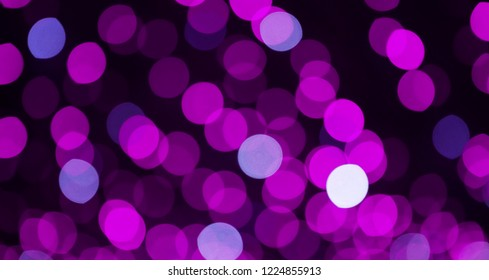 Beautiful Purple lilac Bokeh Background. Decorative Holiday Texture. Backdrop for design. Blurred Festive street light on black Background. Wide Angle Wallpaper