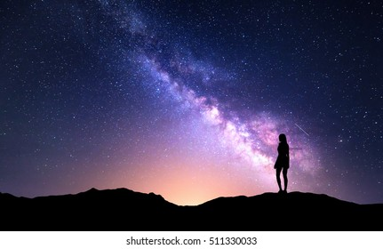 Beautiful purple Milky Way with standing woman. Colorful landscape with night sky with stars and silhouette of a girl on mountain on the background of beautiful galaxy. Milky way with yellow light.