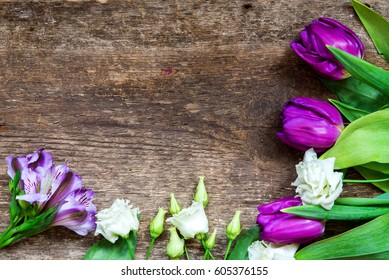 Beautiful purple, pink and white flowers tulips on old wooden background