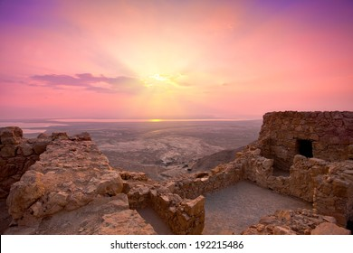 Beautiful purple sunrise over Masada fortress. Ruins of King Herod's palace in Judaean Desert.