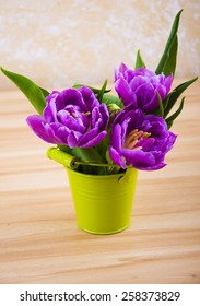 Beautiful purple tulips in a bucket  on a wooden background