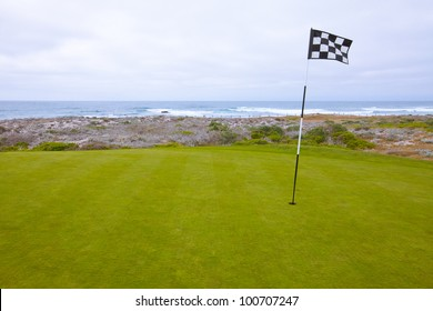 Beautiful putting green and pin flag fluttering in the ocean breeze on a scenic, golf course situated on the Pacific Ocean. Dramatic cloudy sky overhead.
