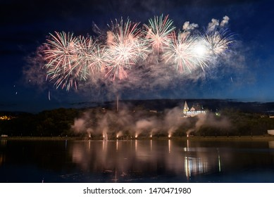 Beautiful pyrotechnic fireworks show in the night sky over the water. Celebration.