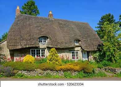 A beautiful quaint Cotswold country Thatched Cottage and garden in summer with blue sky in the heart of The Cotswolds, Gloucestershire, United Kingdom