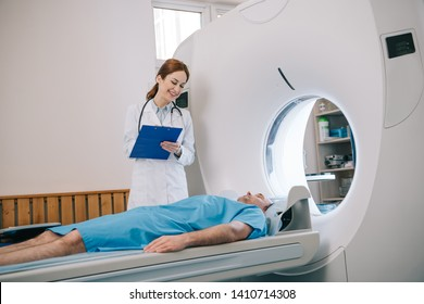 beautiful radiologist holding clipboard while preparing patient for tomography